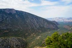 Ny omgeende sikt av dalen för Parnassus berglutning, gröna olivgröna dungar till och med det Ionian havet med ljus himmelbakgrund royaltyfria bilder