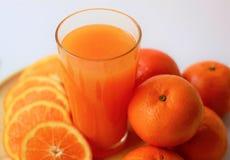 Ny orange fruktsaft för närbild i exponeringsglas, apelsiner och skivor av apelsiner, sunda drinkar, nya vitaminer arkivbild