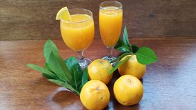 ny orange fruktsaft i exponeringsglaset och den nya orange frukten på det bruna trät arkivbilder