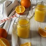 Ny orange fruktsaft i exponeringsglaskrus ?ver vit tr?bakgrund, sikt f?r l?g vinkel close upp arkivfoton