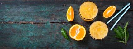 Ny orange fruktsaft med krossad is och nya blåa sugrör för apelsiner och på en exotisk bakgrund för gammal tappning Arkivbilder