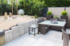 Ny ordnad stenträdgård med terrassen och tabell och stolar arkivbilder
