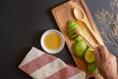 Ny organisk avokado som skivas i halva och honung på svart trät arkivfoto