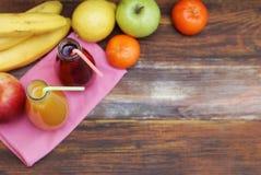 Ny organisk fruktfruktsaft i glasflaska på lantlig träwood bakgrund Den sunda livuppehället bantar och kondition Royaltyfria Bilder