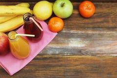 Ny organisk fruktfruktsaft i glasflaska på lantlig träwood bakgrund Den sunda livuppehället bantar och kondition Royaltyfri Bild