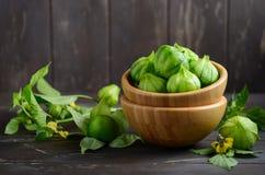 Ny organisk grön tomatillosPhysalisphiladelphica med ett skal på den lantliga trätabellen royaltyfri fotografi