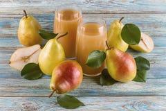 Ny organisk lantgårdpäronfruktsaft i exponeringsglas med rå hela och skivade päron Arkivbild