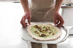 Ny original- italiensk rå pizza, förberedelse i traditionell stil Händer av pizza för kockbagaredanande på kök arkivfoto