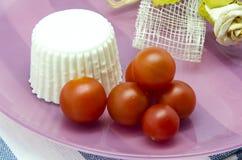 Ny ost med körsbärsröda tomater royaltyfri bild