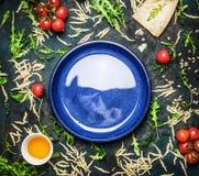 Ny pasta med ingredienser för smaklig matlagning runt om den tomma plattan på lantlig tappningbakgrund, bästa sikt arkivfoto