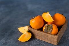 Ny persimonfrukt i en träask på en mörk bakgrund snitt royaltyfri bild