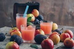 Ny plommonfruktsaft på en trätabell som omges av frukt I bakgrunden är en bröstkorg av frukt Arkivbilder