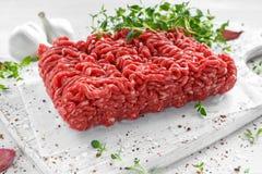 Ny rå nötköttköttfärs med salt, peppar, chili och ny timjan på det vita brädet Royaltyfri Foto