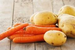 Ny rå potatis och morot på trä Fotografering för Bildbyråer