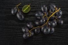 Ny rå svart druva på svart trä Royaltyfria Bilder