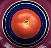 Ny rå tomat på en keramisk platta Fotografering för Bildbyråer
