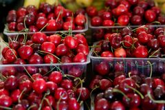 Ny röd körsbär i den plast- asken som är klar för försäljning i fruktmarknaden royaltyfri bild