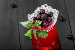 Ny röd lemonad med mintkaramellen, den svarta vinbäret, limefrukt och is i exponeringsglas på mörk bakgrund arkivbild