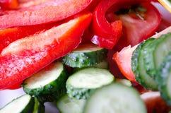 Ny röd peppar och grön gurka på en vit platecloseup royaltyfri foto