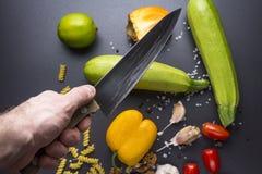 Ny röd pepparpaprika på trä i tappninginställning kökkniven i hand klipper nya grönsaker på den svarta tabellen Zucchinin tomater arkivbilder