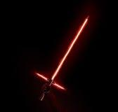 Ny rött ljussabelholdng i hand på svart Arkivfoto