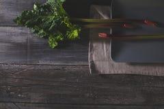 Ny rabarber på grå färgplattan och den gamla trätabellen, lekmanna- lägenhet Arkivfoton