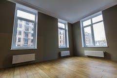 Ny renoverad ruminre med stora fönster som värmer element Arkivfoto
