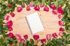 Ny rosa färgrosblomma och tom vit anmärkningsbok på trädäck Arkivbild