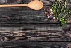 Ny rosmarin, salt, peppar och en sked på en svart träbackg Arkivbild