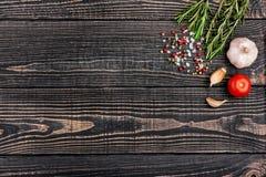 Ny rosmarin, salt, peppar och vitlök på en svart träbackgr Arkivbild
