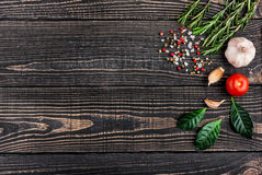 Ny rosmarin, salt, peppar och vitlök på en svart träbackgr Arkivfoton