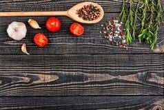 Ny rosmarin, salt, peppar, vitlök och en sked på ett svart trä Arkivbild
