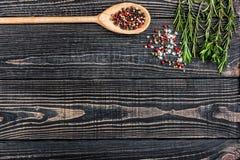 Ny rosmarin, salt, peppar, vitlök och en sked på ett svart trä Arkivbilder