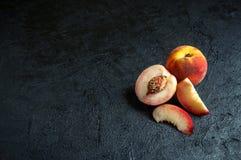 Ny saftig persika och nektarin på mörk bakgrund royaltyfri bild