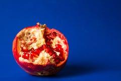 Ny saftig röd granatröttfrukt på blå bakgrund Royaltyfri Bild