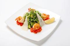 Ny sallad för Arugula med avokadoskivor med parmesanost och stekt räka som smaksättas med balsamic vinäger arkivfoton