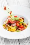 Ny sallad med avokadot, sol torkade tomater, varma peppar, körsbärsröda tomater, söta peppar och löken på träbakgrund Fotografering för Bildbyråer