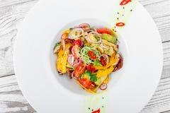 Ny sallad med avokadot, sol torkade tomater, varma peppar, körsbärsröda tomater, söta peppar och löken på träbakgrund Royaltyfria Bilder