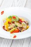 Ny sallad med avokadot, sol torkade tomater, varma peppar, körsbärsröda tomater, söta peppar och löken på träbakgrund Royaltyfri Foto