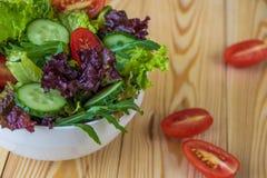 Ny sallad med blandade gräsplaner, den körsbärsröda tomaten och gurkan Royaltyfri Foto
