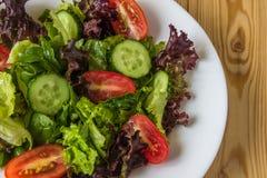 Ny sallad med blandade gräsplaner, den körsbärsröda tomaten och gurkan Arkivbild