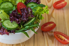 Ny sallad med blandade gräsplaner, den körsbärsröda tomaten och gurkan Arkivfoton