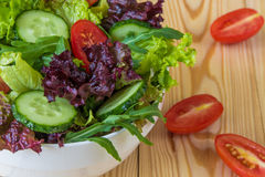 Ny sallad med blandade gräsplaner, den körsbärsröda tomaten och gurkan Arkivfoto