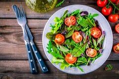 Ny sallad med blandade gräsplaner och körsbärsröd tomat på träbakgrund Arkivbilder