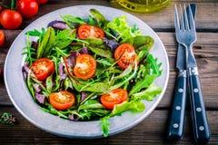 Ny sallad med blandade gräsplaner på träbakgrund Royaltyfri Foto
