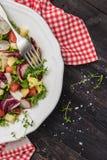 Ny sallad med blandade gräsplaner, rädisan, ost och tomaten i en pl Arkivbilder