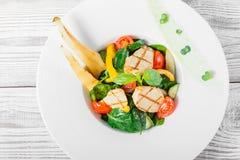 Ny sallad med det fega bröstet, behandla som ett barn spenat, basilika, körsbärsröda tomater, päronet, gurka på plattan på träbak Arkivbild
