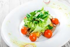 Ny sallad med det fega bröstet, behandla som ett barn spenat, grönsallat, körsbärsröda tomater och ost på träbakgrund Arkivbild