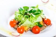 Ny sallad med det fega bröstet, behandla som ett barn spenat, grönsallat, körsbärsröda tomater och ost på träbakgrund Royaltyfri Fotografi