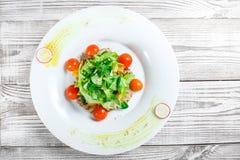 Ny sallad med det fega bröstet, behandla som ett barn spenat, grönsallat, körsbärsröda tomater och ost på träbakgrund Arkivbilder